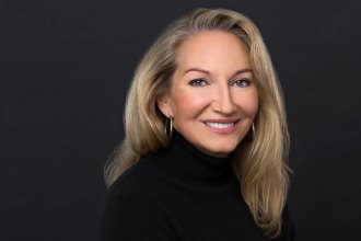 Headshot of wmiling woman with black turtleneck