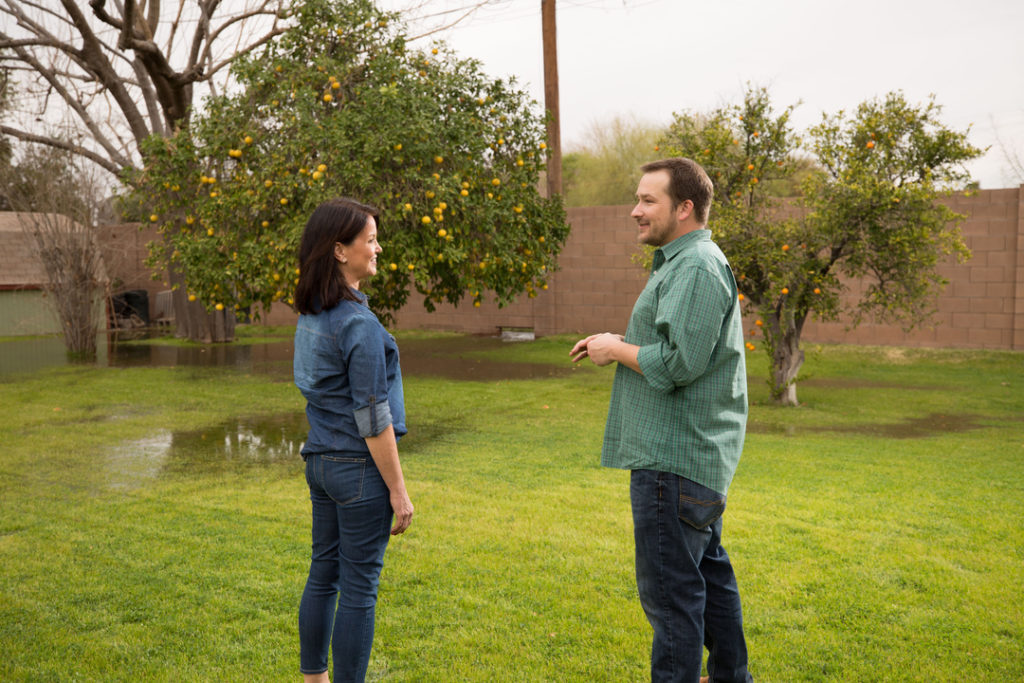 Image of a male and female neighbors discussing irrigation as water is delivered from a back yard valve in Tempe, Ariz.