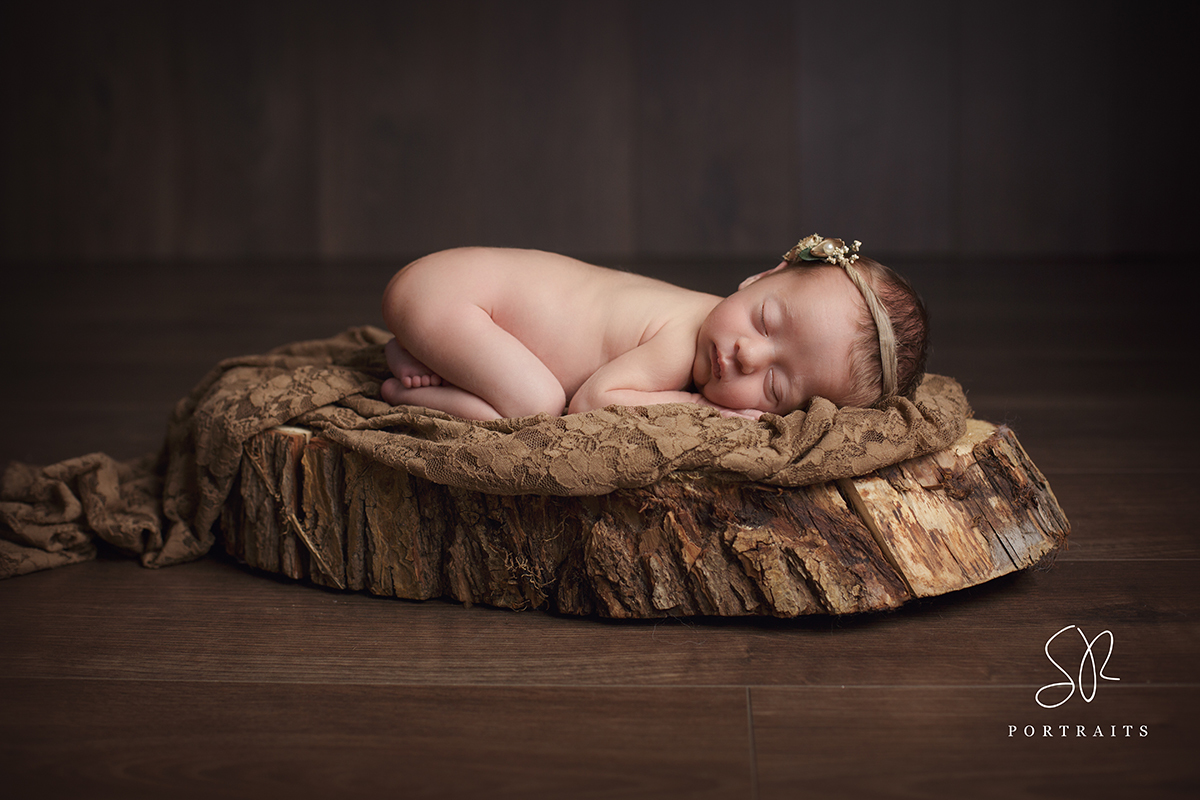 Newborn baby girl on log prop, photography Hucknall