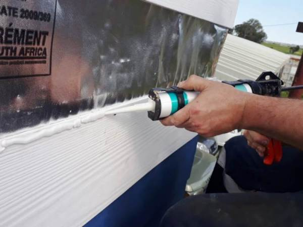 caulking gun with paintable silicon on fibre cement board