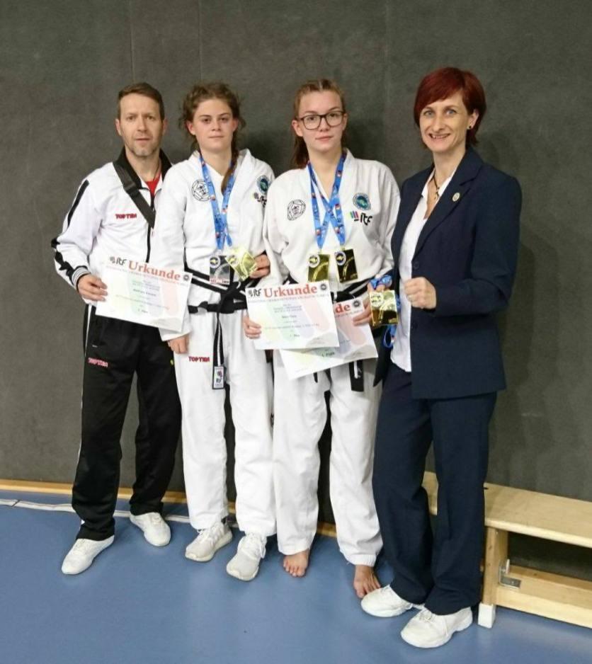 Trainer Frank Becher (4. Dan) mit Vanessa Mühlhans (1. Dan), Cora Braun (1. Dan) und Kampfrichterin Anke Habich (3. Dan) (v.l.n.r.)