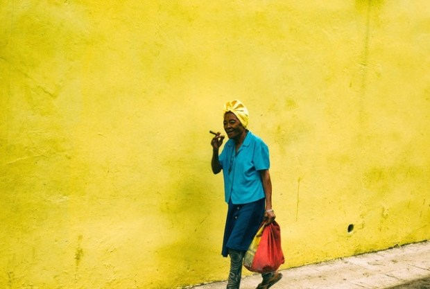 Lady with cigar walking past a bright yellow wall, Havana