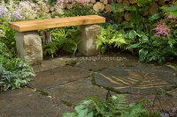 Wooden and stone garden bench on stone patio with leaf ...
