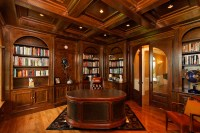 Traditional home office/library with dark paneling and ...