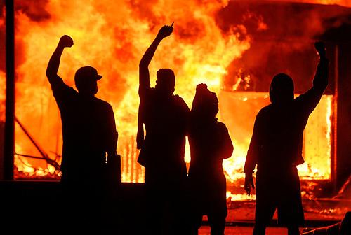 MINEÁPOLIS (ESTADOS UNIDOS), 30/05/2020.- Manifestantes alzan el puño junto a una tienda en llamas, durante unos disturbios provocados tras la muerte del afroamericano George Floyd a manos de la policía el lunes pasado en Mineápolis, este sábado en Mineápolis, Minnesota, Estados Unidos. Los disturbios raciales por la muerte del afroamericano George Floyd a manos de la policía el lunes pasado en Mineápolis, se extendieron por ciudades de todo Estados Unidos, con incendios, saqueos y enfrentamientos entre manifestantes y agentes antidisturbios. Floyd, de 40 años, falleció el lunes cuando era detenido bajo la sospecha de haber intentado usar un billete falso de 20 dólares en un supermercado. EFE/Craig Lassig