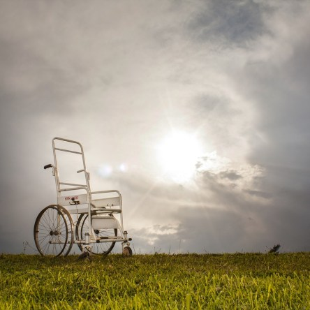 a wheelchair stands alone on a hill