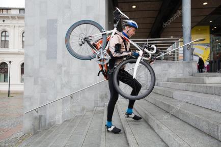 Ciclista hombre con bicicleta al hombro subiendo gradas.