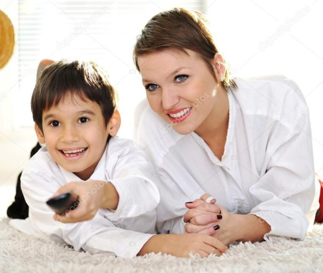 Mom With Son Lying On Floor And Watching Tv Using Remote Control Stock Photo
