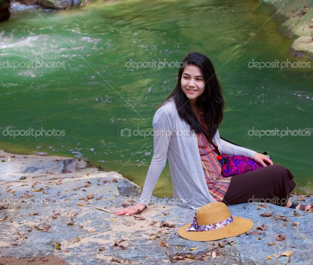 Biracial Teen Girl Sitting By A River In Norhtern Thailand Stock Photo