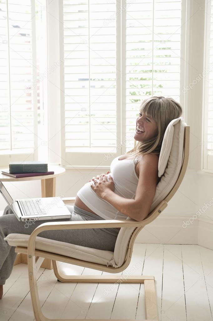 Pregnant woman sitting on chair touching stomach  Stock