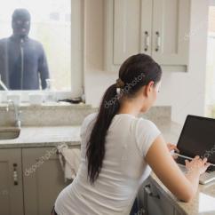 Kitchen Window Treatments Ideas Aid Mixer 看着女人通过窗口使用便携式计算机的强盗 图库照片 C Wavebreakmedia 看着女人在厨房里通过窗口使用便携式计算机的强盗 照片作者wavebreakmedia
