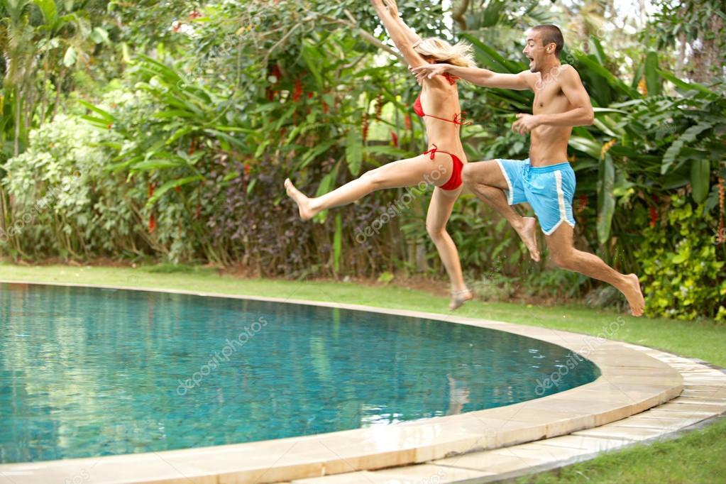 Jonge Plezier Paar Springen In Een Tropisch Zwembad Stockfoto