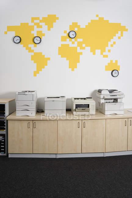row photocopiers by wall