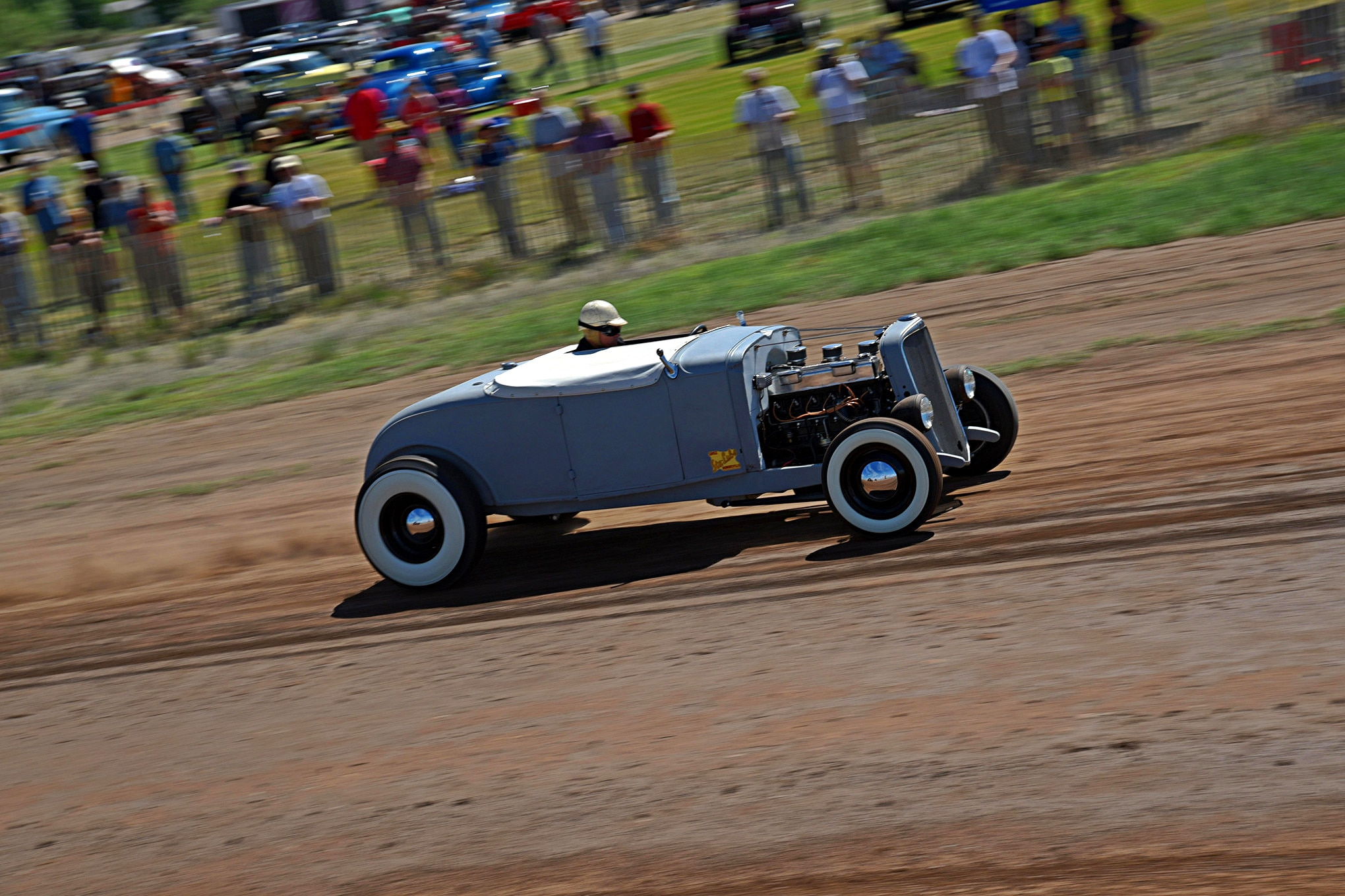 """Six Shooter: Dave Overholt and his trusty '31 Chevy roadster seem to appear at every event west of the Mississippi. It's always a strong runner, and its owner constantly pushes her to the limit whenever he's on a track—paved or dirt. The Bow Tie started down the hot rod path in the '60s when the doors received a suicide fit, but then the project stalled. Dave got a tip from local legend Gary Vahling about the car and then scored the needy roadster. The engine is an early 292 straight-six. It's a stock block, but the compression has been boosted to 10:1 by a highly modified 194ci head. A custom Clay Smith cam gets the valves jumping. Three Rochesters are up on top, connected to an original Offenhauser 3x1 intake. A vintage Mallory Double Life distributor gets the spark out, and those pipes are early Clifford issue. A '57 Ford rear with 4.56 gears gets the power to the back wheels, a 4-inch drop axle gives him a nice rake up front, and stopping power is via Ford hydraulic brakes with Buick drums. The body is basically the same as the day he bought it. Sparse interior with a few period Stewart-Warner gauges makes this hot rod look the part. His son's chalk writing of """"Hot Rod"""" is still on the dash, and Beth Kearney of Lil' Dame pinstriping did the work on the decklid in remembrance of Dave's brother."""