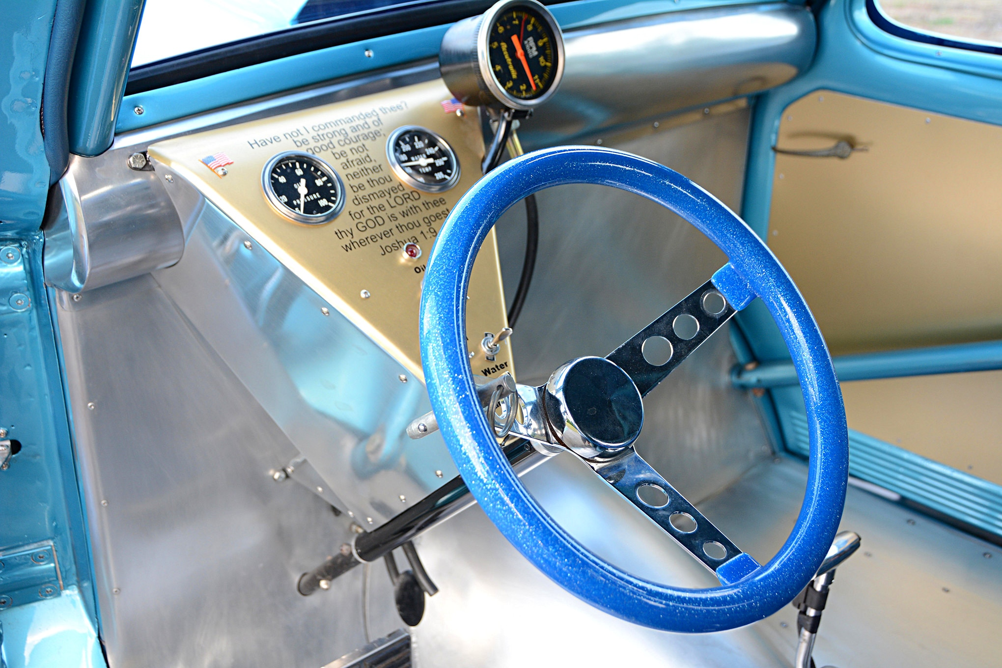 A blue metalflake steering wheel is the centerpiece in this basic race car interior, as it stands out in a sea of bare aluminum. The custom dash panel holds a couple gauges, a mount for the cable-drive Accutronic tachometer and a special Bible verse that Gene holds dear.