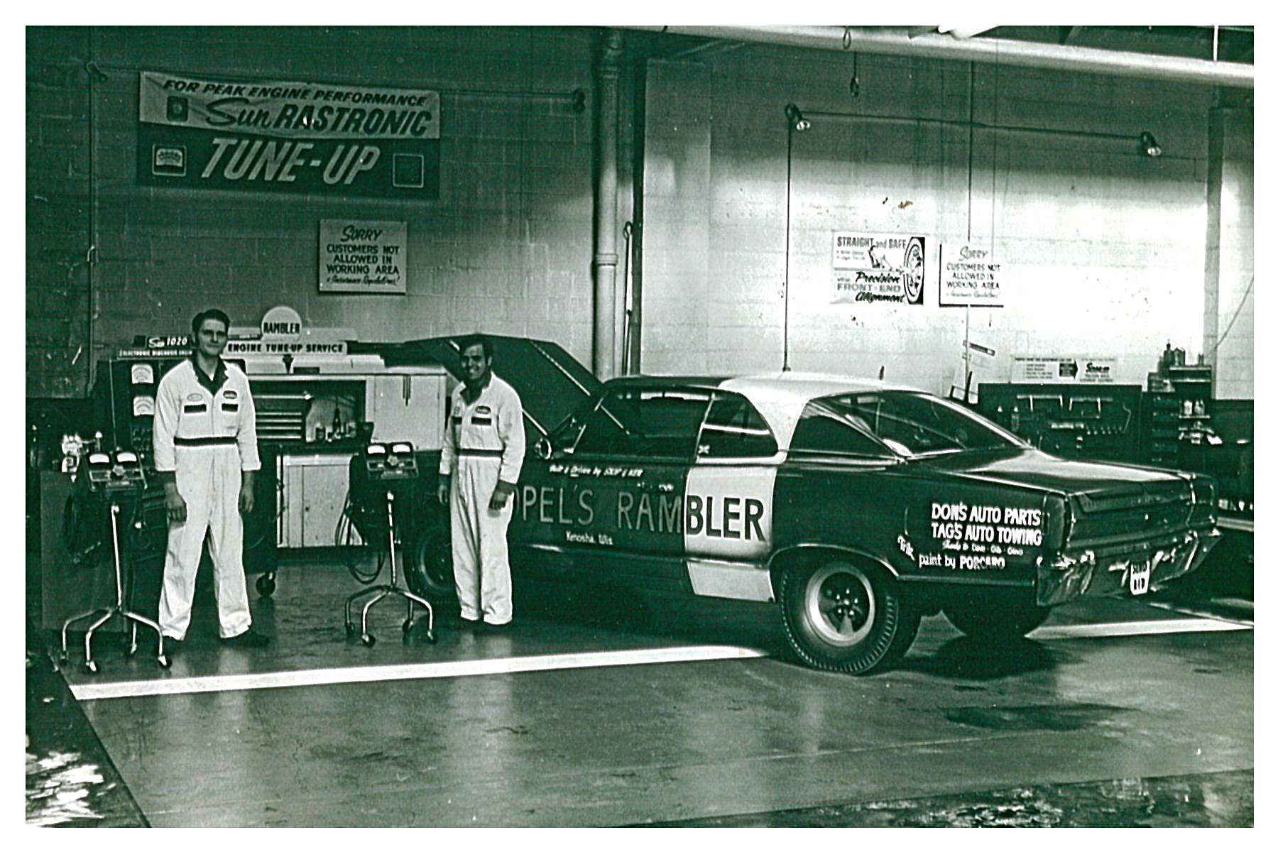 Topel Rambler Line Mechanic Bernie Pucci and Dave Graves pose alongside the dealership's 1967 Rebel Super Stocker while it is serviced. Note that the earliest version makes use of American mag wheels.