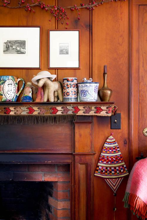 Painel antigo de madeira cobre a lareira na sala e objetos trazidos de viagem dão toque pessoal à decoração