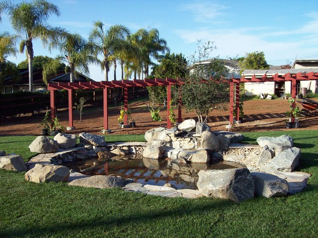 Rural backyard featuring water feature and grape arbor