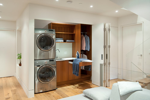 Efficient hall closet laundry area with pull out ironing board featured on Remodelaholic.com