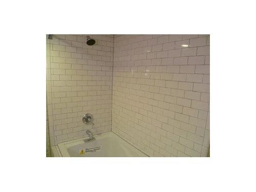 glass accent wall in a white subway tub