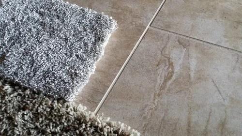 gray carpet next to tan tile
