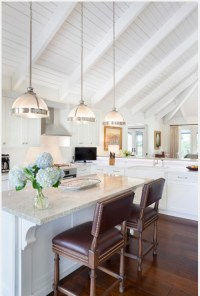 Three white half ball pendant lights hang from a tall ...