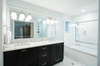 Traditional master bathroom with dark cabinets and white ...