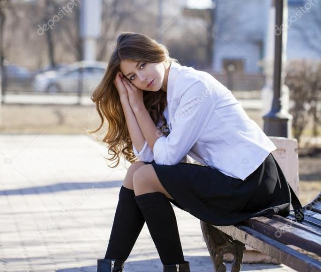 Young Beautiful Blonde Schoolgirl Sitting On A Bench Stock Photo