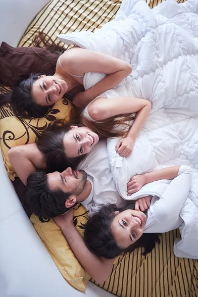 bed with three beautiful women