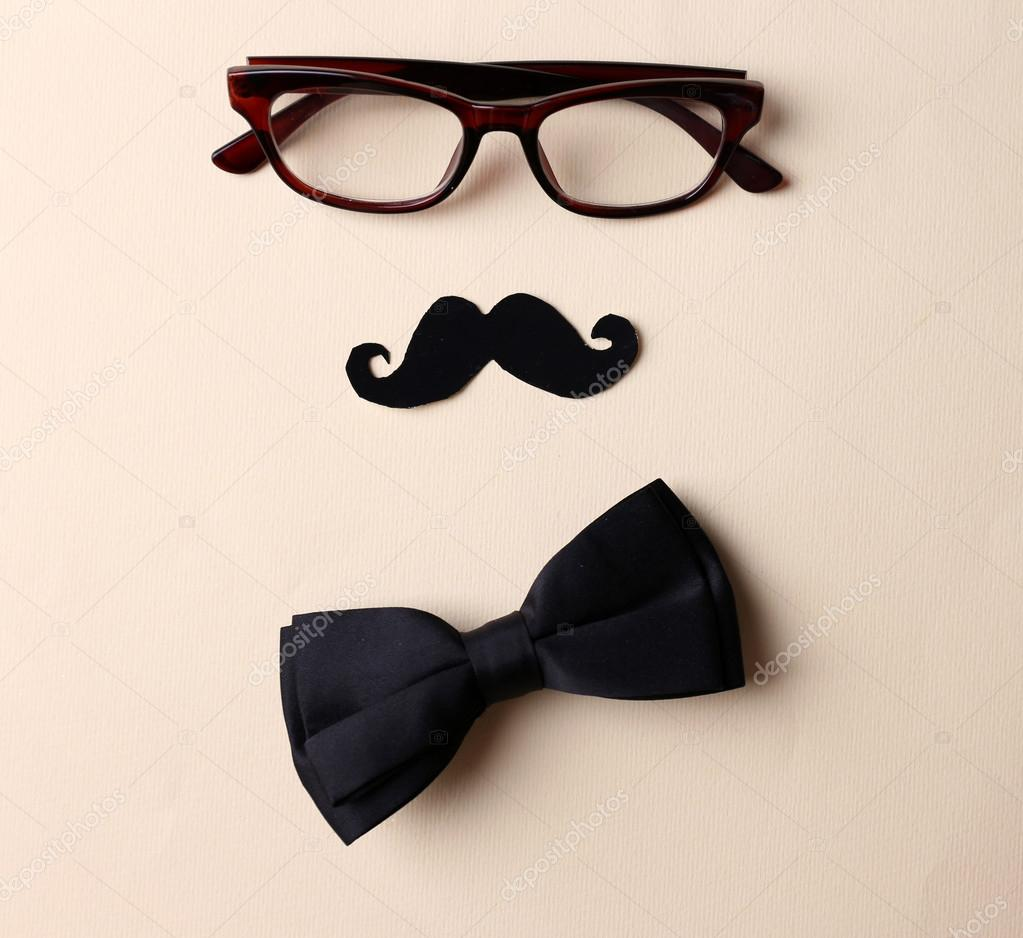 Glasses, mustache and bow tie forming man face on beige