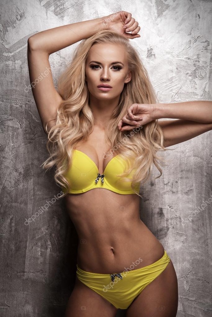 Sensuele mooie blonde vrouw poseren in gele lingerie op