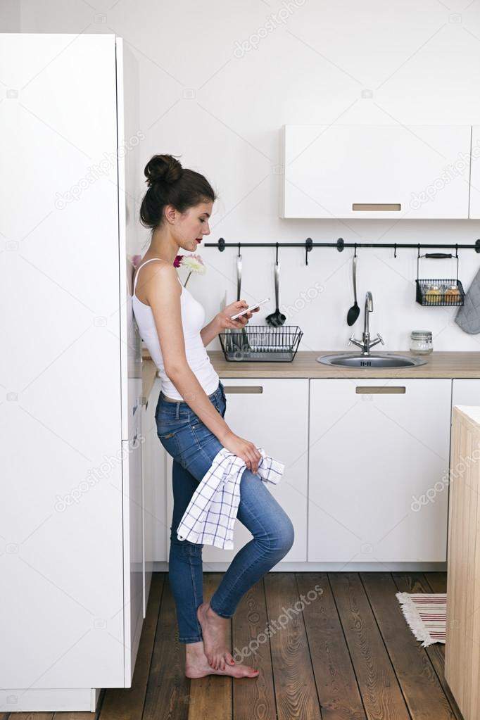 kitchen phone stainless steel barefoot girl using cell in stock photo