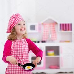 Kids Wooden Kitchen Pantry Shelves 小女孩玩玩具厨房 图库照片 C Famveldman 114350796 在厨师帽和围裙烹饪玩具厨房里的煎的鸡蛋的小女孩 幼儿的木制玩具 孩子们玩耍和厨师在家里或日托 蹒跚学步的孩子玩炉 餐具 盘子和碗
