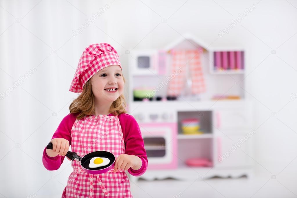kids wooden kitchen paint colors 小女孩玩玩具厨房 图库照片 c famveldman 114351516 在厨师帽和围裙烹饪玩具厨房里的煎的鸡蛋的小女孩 幼儿的木制玩具 孩子们玩耍和厨师在家里或日托 蹒跚学步的孩子玩炉 餐具 盘子和碗