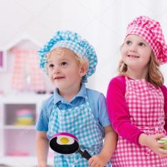Kids Wooden Kitchen Shelves For Cabinets 孩子玩玩具厨房 图库照片 C Famveldman 114588868 小女孩和男孩在厨师帽和围裙烹饪玩具厨房里的煎的鸡蛋 幼儿的木制玩具 孩子们玩耍和厨师在家里或日托 蹒跚学步的宝宝在玩与炉子 盘子和碗