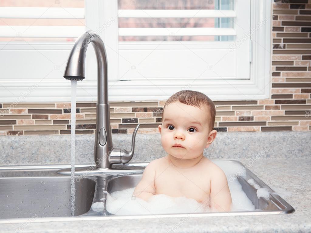 deep kitchen sink unfinished wall cabinets 可爱的白种人有趣的婴儿女孩男孩与深黑色的眼睛 坐在靠近窗口看着别处 泡沫和水的大厨房水槽里生活日常概念的肖像