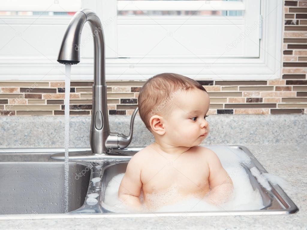 deep kitchen sink rohl sinks 可爱的白种人有趣的婴儿女孩男孩与深黑色的眼睛 坐在靠近窗口看着别处 泡沫和水的大厨房水槽里生活日常概念的肖像