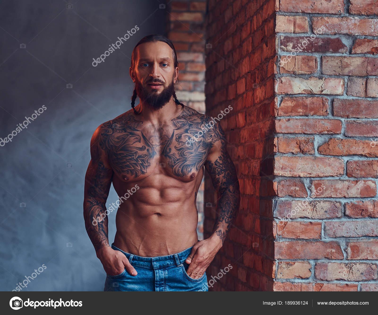 beau male torse nu tatoue avec elegant coupe de cheveux et barbe debout appuye contre un mur de briques dans une cuisine image de fxquadro