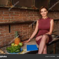 Nice Kitchen Tables Gray Table 坐在厨房桌子上的漂亮女人拿着笔记本 在砖墙背景上摆出笑脸的年轻女性 在砖墙背景