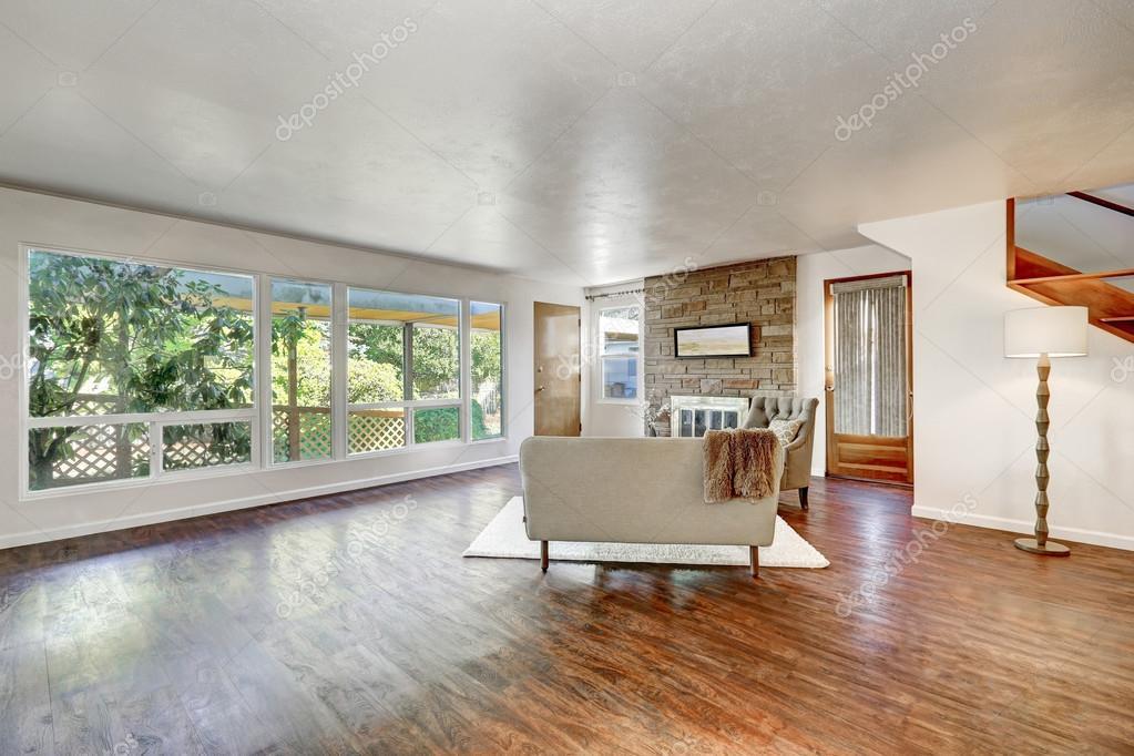 Ruime woonkamer met grote ramen en gepolijst hardhouten