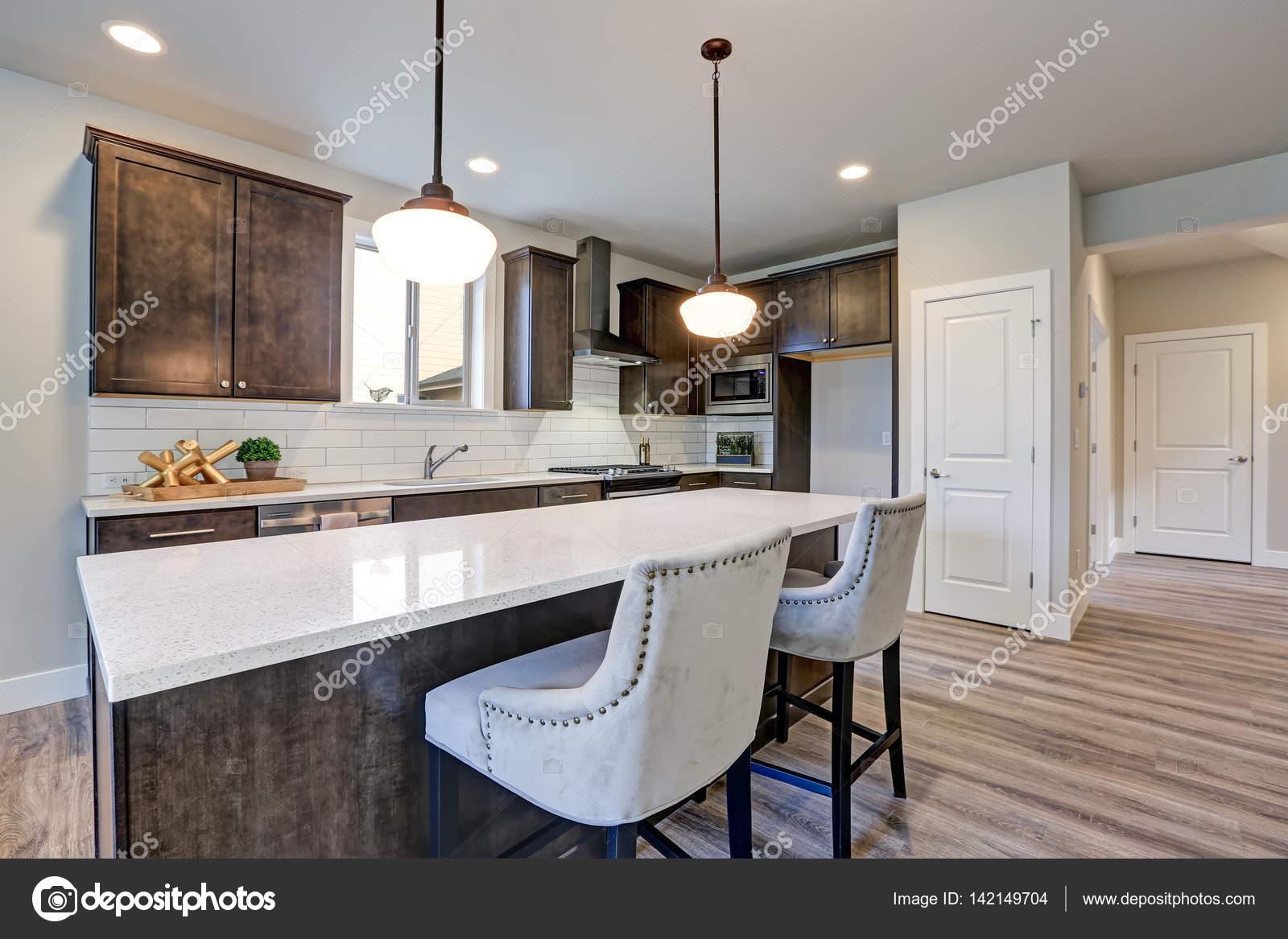 islands kitchen vent fan 新厨房拥有黑暗的实木橱柜 大岛 图库照片 c iriana88w 142149704 白色后挡板地铁瓷砖 在大小岛屿与白色和灰色石英计数器被垂饰灯照射 西北美国 照片作者iriana88w
