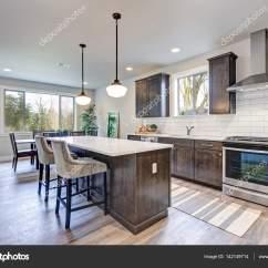 Grey Kitchen Backsplash Cost Of Replacing Cabinets 新厨房拥有黑暗的实木橱柜 大岛 图库照片 C Iriana88w 142149714 白色后挡板地铁瓷砖 在大小岛屿与白色和灰色石英计数器被垂饰灯照射 西北美国 照片作者iriana88w