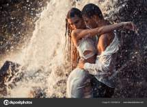 Young Enamored Couple Hugs Under Spray Of Waterfall