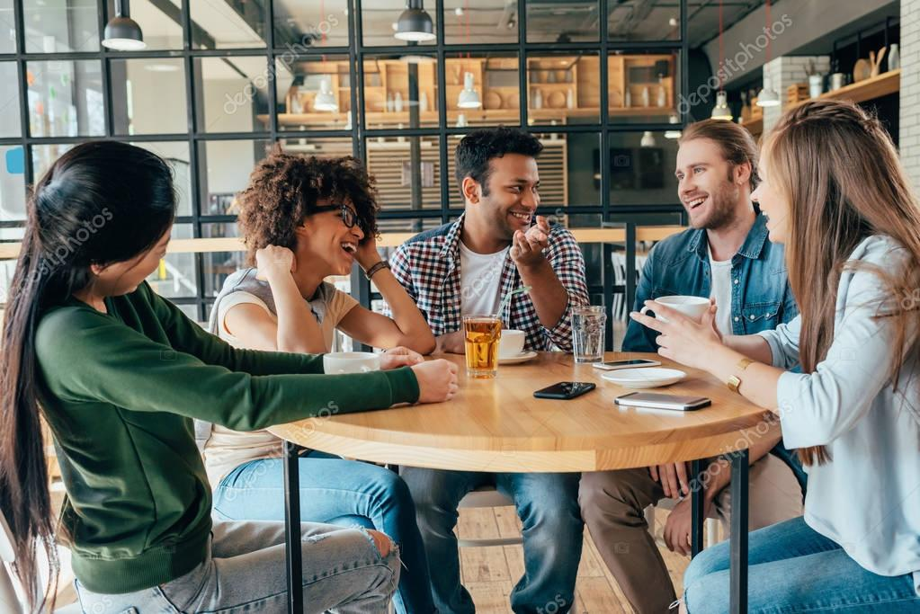 Friends spending time together in cafe — Stock Photo © NatashaFedorova #160868652