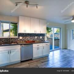 Mosaic Backsplash Kitchen Small Table Sets L 型厨房房设计 图库照片 C Alabn 180155268 形厨房房设计用白色橱柜 棕花岗岩台面 马赛克后 内置不锈钢器具 宽木板硬木地板 厨房有出口到一个小阳台 照片作者alabn