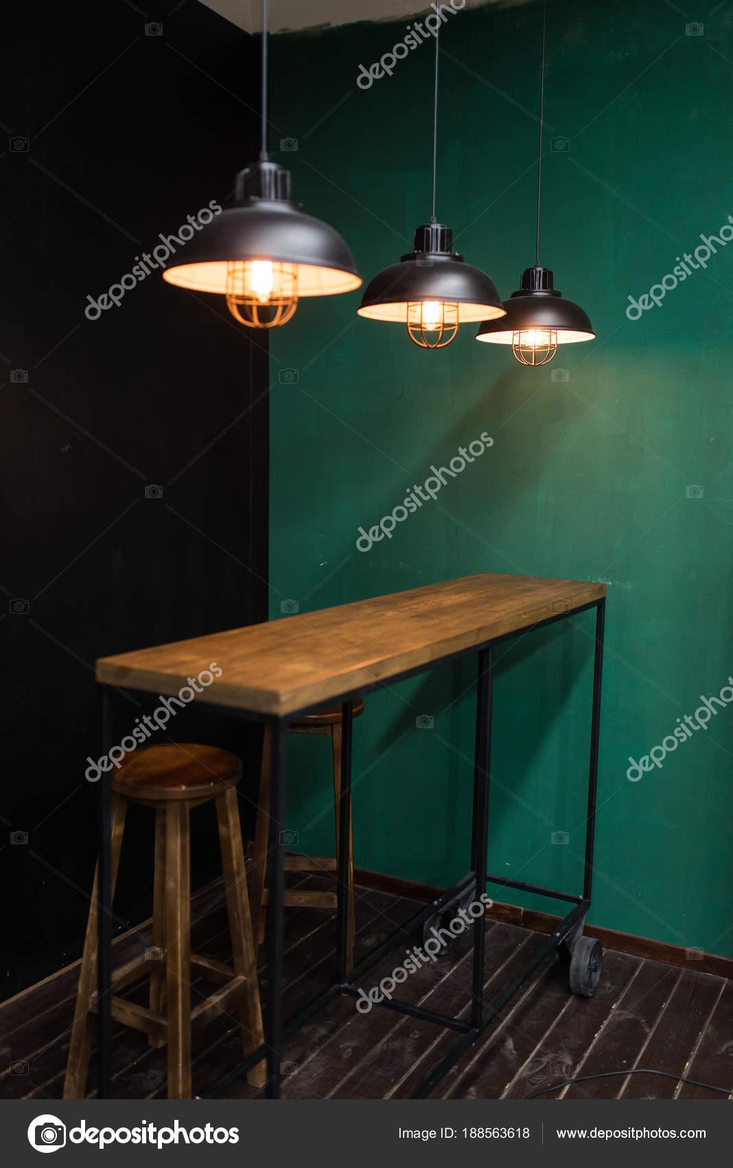 kitchen bar lights oak cabinet doors 在厨房的车轮上的酒吧架上挂灯和木制酒吧凳子在绿色和黑色的墙壁的背景下 在厨房的车轮上的酒吧架上挂灯和木制酒吧凳子