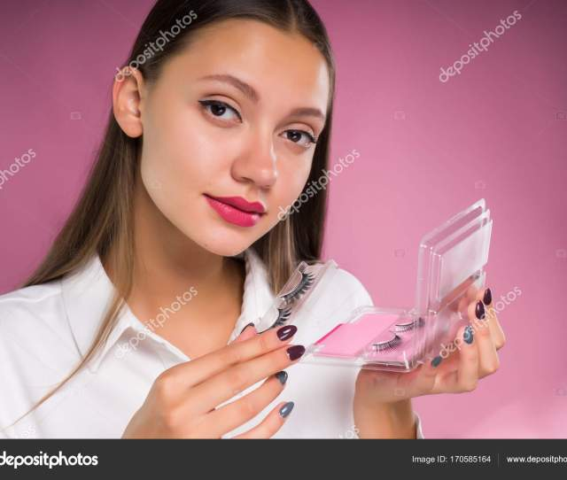 Young Beautiful Girl Holding A Package With Black Overhead Ladders Stock Photo