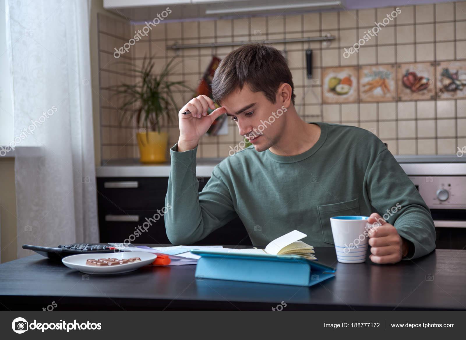 kitchen calculator cabinet on wheels 一个有深思熟虑的焦虑表情的年轻人坐在厨房的桌子上 用计算器和笔记本 用计算器和笔记本来计算家庭预算和当前支出 照片作者sky dog