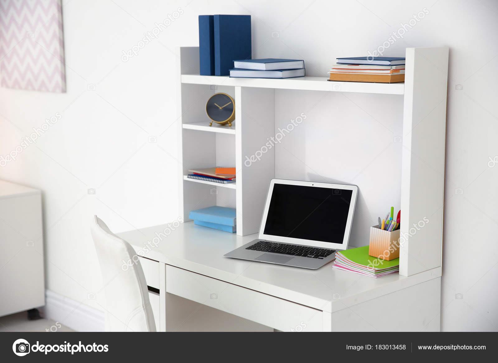 Mesa de ordenador porttil y libros junto a la pared