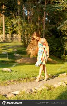 Young Girl Walks Park Barefoot In Bright Sun